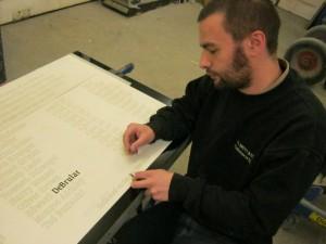 Engraver works on Garveston Twelve Memorial Stone, beginning with the name of lost airman, Pete DeBrular.